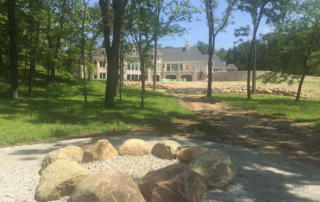 Rear view of Custom Home - Firepit in woods