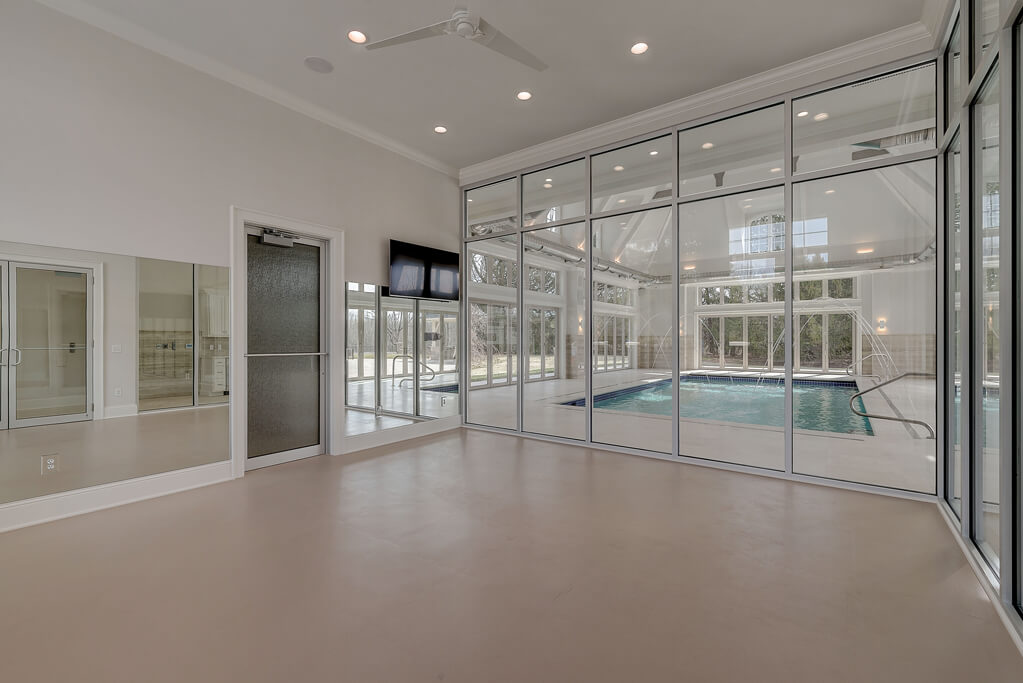 Ennis Custom Homes - Indoor Pool Wing - Exercise Room - Spa Shower - Luxury Home Builder in Carmel, Indiana - Exercise Room Looking into Pool 1